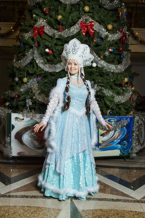 snegurochka: New Year. Girl dressed in traditional Russian costume Christmas Snow Maiden on a background of the Christmas tree Stock Photo