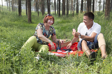 Family, an elderly woman and her son in a park on the weekend activities. An elderly woman and her son make a picnic in the woods. A card game for fun. The concept of retirement age and filial love.