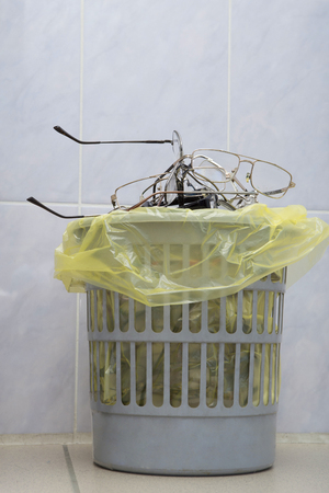 Pile of used glasses in a trash can