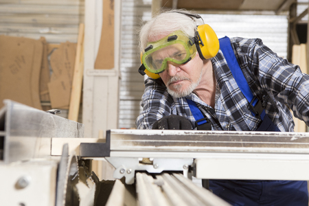 Worker using saw machine to make furniture at carpenters workshop. Handmade business at small furniture factory. Stock Photo