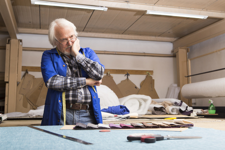 tailor seat: The designer reflects on the design of the furniture, chooses the color of the finishing material behind the cutting table in the workshop of a small furniture factory