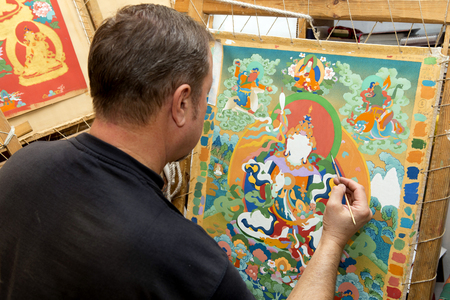 iconography: The artist sitting cross-legged in the lotus pose draws a Buddhist icon of the tank with a thin column brush in the art workshop. Stock Photo