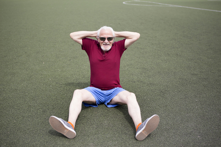availability: The senior man is practicing at a sports stadium in the open air. The concept of a healthy lifestyle and the availability of sports training for every person. Available sports equipment in a public place.