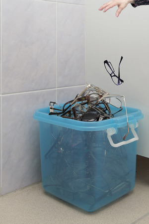 The cured patient of the ophthalmologist throws away unnecessary glasses in the garbage container after the operation for restoring vision. Stock Photo