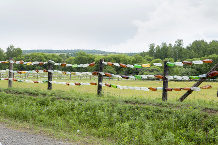 barbed wire fence: An original fence of multi-colored plastic bottles. Fence from cattle in the field of grass in Siberia.