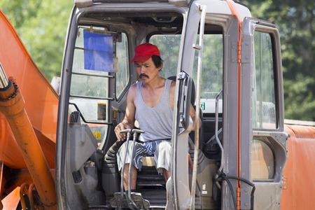 Driver - excavator driver in the cabin controls the process of moving the ground. Stock Photo
