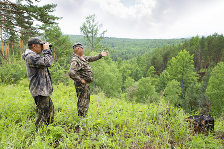 Foresters went to the protection of the forest. An adult male forester examines the forest from the top of the mountain through binoculars. The huntsman shows the directions of the brown bear habitat. Stock Photo