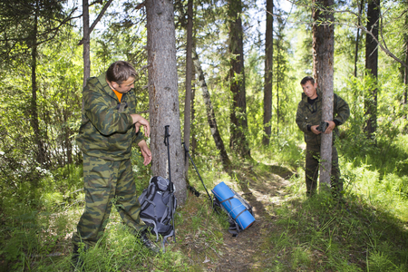 Camera traps with infrared light and a motion detector attached by straps on a tree photograph animals in the Siberian taiga. Foresters install photo traps on a tree for automatic photographing or video shooting of wildlife in the forest.