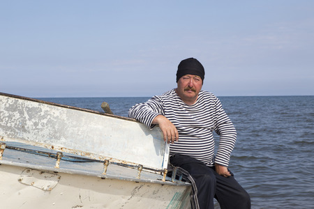 Portrait of a mature man on a light dyural boat on the shore of Lake Baikal. The skipper sits on the bow of the boat on the shore of Lake Baikal.