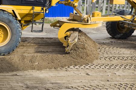 모터 그레이더는 비포장 도로를 정렬합니다. 양동이로 움직이는 바퀴에 불도저입니다. 휠 트랙터는 건설 현장에서 양동이로 자갈을 움직입니다. 푸른  스톡 콘텐츠