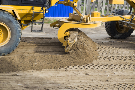 The motor grader aligns the dirt road. A bulldozer on wheels moving with a bucket. The wheel tractor moves the gravel with a bucket on the construction site. Blue sky and white clouds in the background.