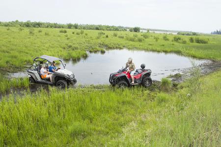 Aventuras para adultos: un viaje en cuatriciclos en caminos rurales no transitables. Los turistas en ATV en cascos de protección de huelgas y suciedad, participan en la carrera todo terreno en el bosque en un caluroso día de verano. Foto de archivo