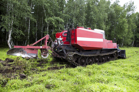 The skid tractor opens the fire-prevention strip. The skidder tractor cuts with a knife and sends the top layer of soil with the grass to the heap. Prevention of fires in the forest. Stock Photo