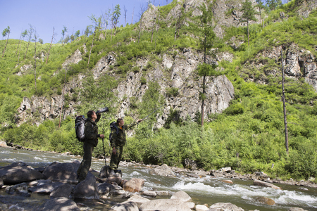 The forester and the inspector with a backpack, sleeping mat behind his back and a rifle in the trek across the mountain river, flowing among the stones in the forest