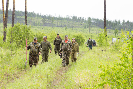 A group of forest workers in protective encephalitic clothing passes through the taiga in rubber boots, with shovels, saws and other tools for forest inspection. Summer weather. Front view. Stock Photo