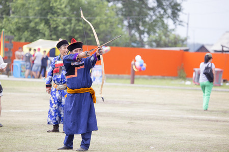 Competitions in shooting from a sports bow in Siberia. Mongolian competitions in archery. The sportsman is dressed in a traditional Buryat-Mongolian suit, shooting with his arrows during a national holiday.