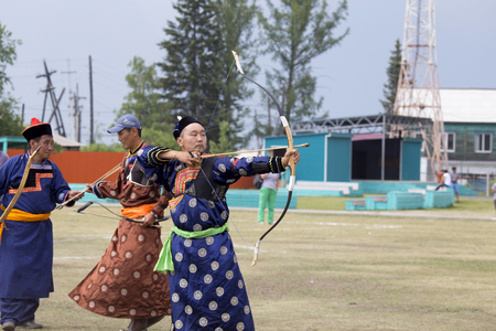 Competitions in shooting from a sports bow in Siberia. Mongolian competitions in archery. The sportsman is dressed in a traditional Buryat-Mongolian suit, shooting with his arrows during a national ho 報道画像
