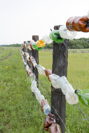 An original fence of multi-colored plastic bottles. Fence from cattle in the field of grass in Siberia.