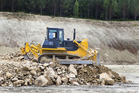 The bulldozer moves and spreads the soil and rubble on the embankment of the road.