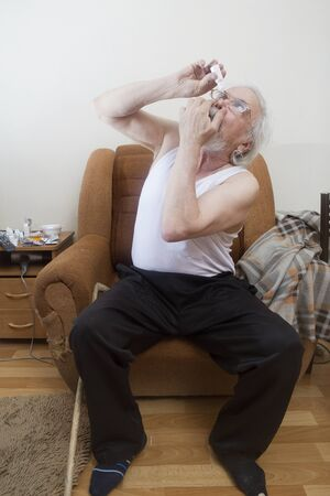 The old sick man independently conducts treatment of senile cataract and glaucoma, instills eye drops into his eyes.