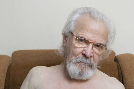 A lonely sick poor old man suffering from eye diseases, independently engaged in conservative treatment of cataract and glaucoma. Stock Photo