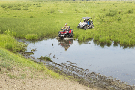 Adventures for adults - a trip on ATVs on not passable rural roads. Tourists on ATV in protective helmets from strikes and dirt, participate in the off-road race in the forest on a hot summer day. Stock Photo