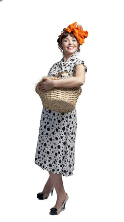 Young girl in a pea dress and bow on head holding a basket with a white background posing and dancing in the studio in front of the camera