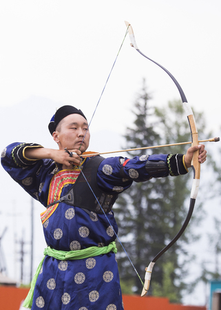 Competitions in shooting from a sports bow in Siberia. Mongolian competitions in archery. The sportsman is dressed in a traditional Buryat-Mongolian suit, shooting with his arrows during a national ho 写真素材
