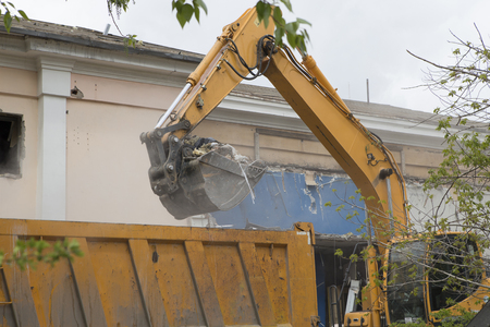 Excavator on wheels do the loading of construction debris and debris of the walls of the old building after the destruction, in the body of a dump truck 版權商用圖片