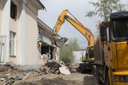 Excavator on wheels do the loading of construction debris and debris of the walls of the old building after the destruction, in the body of a dump truck Archivio Fotografico