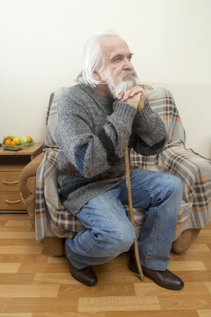 A sad sick old man in an orphanage for the elderly sits in a chair all alone and reflects on the past years Stock Photo