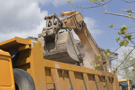 Excavator on wheels do the loading of construction debris and debris of the walls of the old building after the destruction, in the body of a dump truck Stock Photo