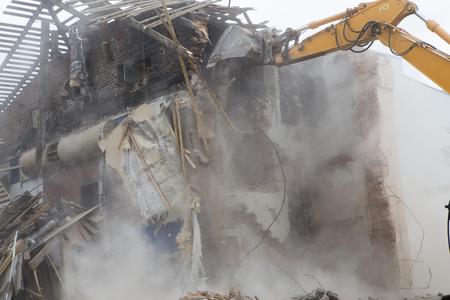 Het vernietigen van de muren van het oude gebouw en het opruimen van bouwafval met een emmer van een graafmachine. Stockfoto