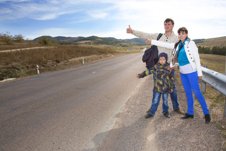 A friendly family of three people, the father of mother and son, travel around the world hitchhiking during the holidays and catch cars on the highway in the valley. Stock Photo