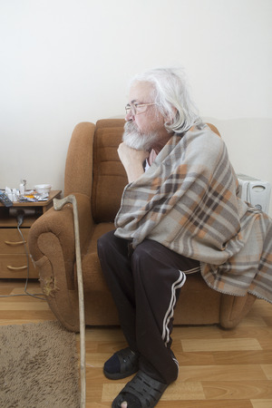 An old lonely sick poor man, suffering from eye disease with cataracts and glaucoma, sits in a chair all alone.