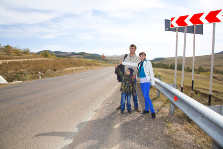 A friendly family of three people, the father of mother and son, travel around the world hitchhiking during the holidays and catch cars on the highway in the valley. Imagens