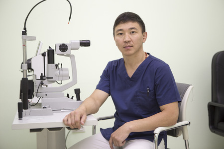 Asian male ophthalmologist is at his workplace working with the device