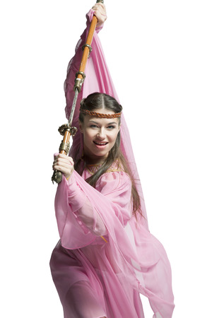 Middle Ages warrior girl in leather armor with a sword and scabbard in a transparent pink dress