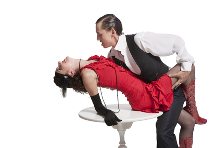 Young couple guy and girl in retro style perform a tango in a sexy pose carved on a white background and passionately love each other Archivio Fotografico