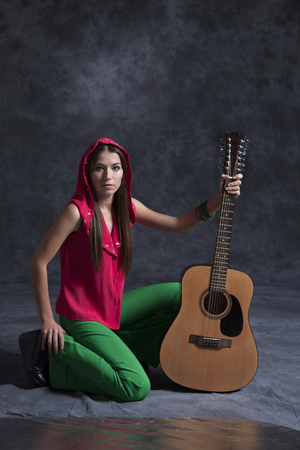 A young girl plays the guitar and sings funny rock and sad romances