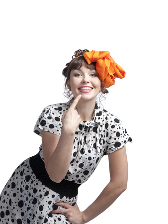 A young girl in a summer dress made of cloth in polka dots and a bow in her hair, dancing with a basket in her hands and posing in the studio on a white background.