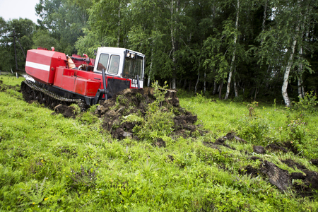 The skid tractor opens the fire-prevention strip. The skidder tractor cuts with a knife and sends the top layer of soil with the grass to the heap. Prevention of fires in the forest. Reklamní fotografie
