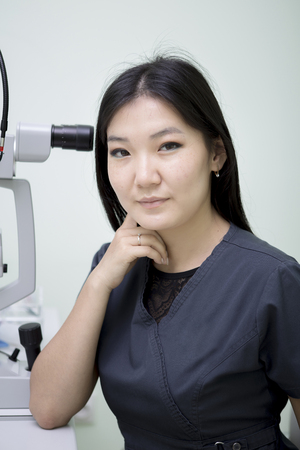 Asian girl ophthalmologist at her workplace working with device