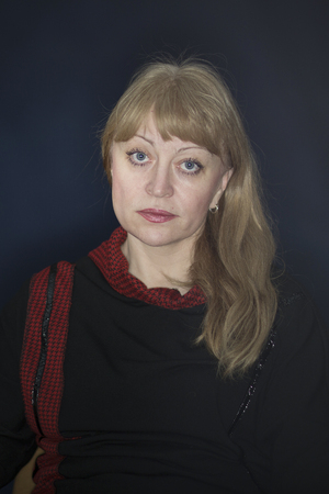Portrait of a beautiful fifty-year-old blonde on a dark background with classic facial features and blue eyes underlined with light Фото со стока