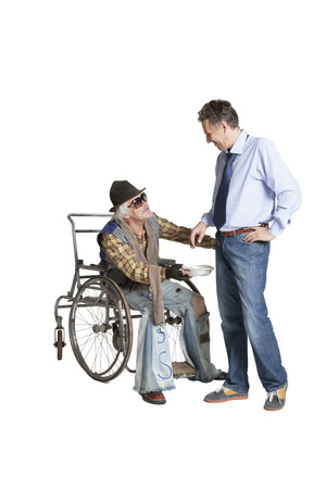 A successful manager, laughing and mocking, gives a beggar sitting in a wheelchair a dollar bill 版權商用圖片