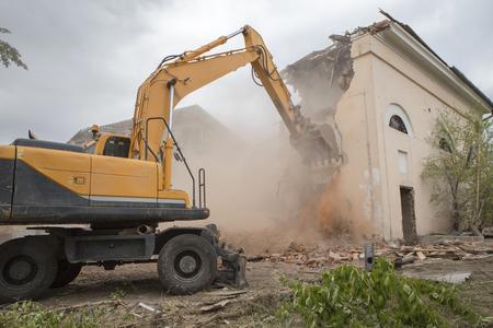 Die Zerstörung der Mauern des alten Gebäudes und die Reinigung von Bauschutt mit einem Eimer eines Baggers.