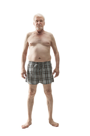 Elderly man posing in the studio in the nude cut out on a white background 免版税图像