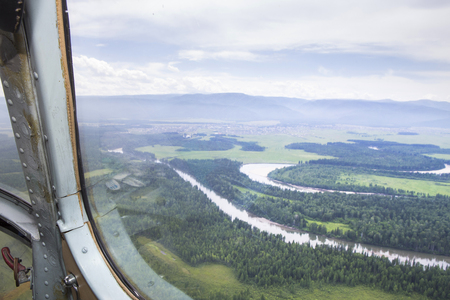 The rivers and lakes of Eastern Siberia from the altitude. A view from the cockpit of the helicopter to the lakes and the river in the Siberian taiga.