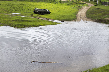 An off-road vehicle on leaves the river. The cross-country vehicle on the crosses the river. An off-road vehicle sails on the river.