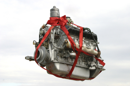 A gift in the form of a truck engine decorated with fresh flowers is floating in the sky against a background of clouds.